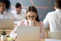 Серьезный женский работник наслаждаясь кофе пока работающ на компьтер-книжке Стоковое Фото