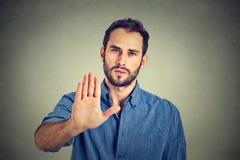 Серьезный жест стопа показа человека изолированный на серой предпосылке стены Стоковые Изображения RF