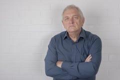Серьезный зрелый человек с белой предпосылкой кирпича Стоковое фото RF