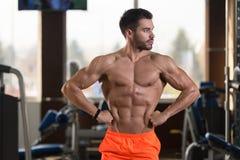 Серьезный культурист стоя в спортзале стоковая фотография