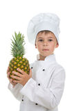 Серьезный мальчик в белой форме шеф-повара держит свежий ананас на белой предпосылке Стоковое Изображение