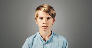 Серьезный мальчик изолированный на предпосылке видеоматериал