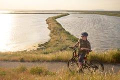 Серьезный мальчик ехать его горный велосипед на заходе солнца Стоковая Фотография RF