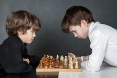 Серьезный мальчик 2 играя шахмат, студию стоковые фотографии rf