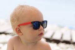 Серьезный милый малыш в солнечных очках на пляже Стоковая Фотография RF