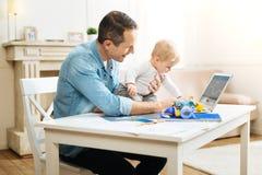 Серьезный младенец исследуя детали на таблице пока был с отцом Стоковое Фото