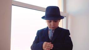 Серьезный молодой мальчик в деловом костюме и шляпе смотря наручные часы на предпосылке окна в офисе Мальчик дела портрета сток-видео