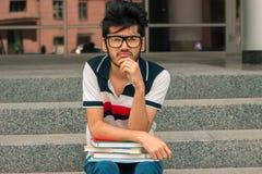 Серьезный молодой студент в стеклах сидит на лестницах стоковое изображение rf