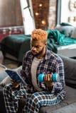 Серьезный молодой человек будучи включанным в чтение стоковое изображение