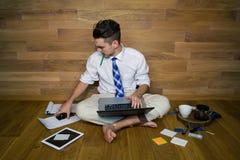 Серьезный молодой человек в смешных одеждах сидит на поле против стены и работает с компьтер-книжкой Стоковая Фотография