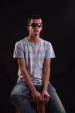 Серьезный молодой человек при солнечные очки сидя на стуле стоковая фотография rf