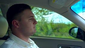 Серьезный молодой человек управляя автомобилем акции видеоматериалы