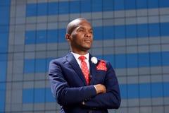 Серьезный молодой африканский бизнесмен стоя в городе Стоковые Изображения