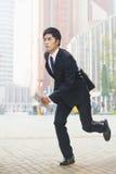 Серьезный, молодой бизнесмен в костюме бежать в финансовом районе в Пекине, Китае Стоковое фото RF