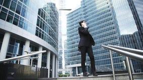 Серьезный молодой бизнесмен в стеклах говоря на его телефоне в центре города видеоматериал