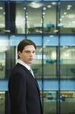Серьезный молодой бизнесмен стоя в офисе Стоковое Изображение