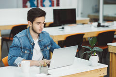 Серьезный молодой парень при борода работая на компьтер-книжке стоковое фото rf