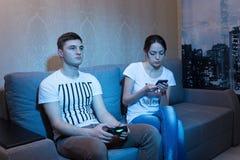 Серьезный молодой человек играя видеоигру сидя с его girlfrie стоковые фотографии rf