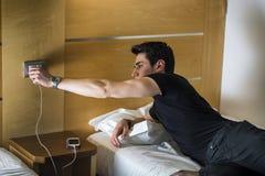 Серьезный молодой человек соединяя телефон к заряжателю Стоковое Изображение RF
