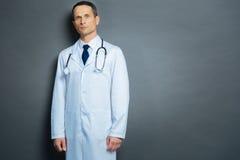 Серьезный мужской врач представляя для камеры над серой предпосылкой стоковое изображение rf