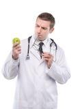 Серьезный мужской доктор смотря зеленое яблоко Стоковая Фотография