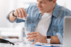 Серьезный мужск человек добавляя порошок к воде Стоковое Изображение RF