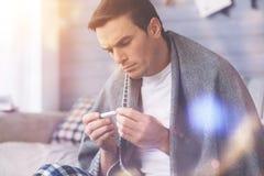 Серьезный мужск человек смотря термометр Стоковые Фото
