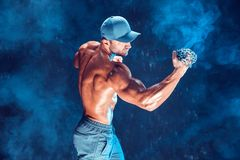 Серьезный мышечный боец делая пунш при цепи заплетенные над его кулаком в дыме стоковые фотографии rf