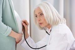 Серьезный доктор с животом стетоскопа слушая беременной женщины Стоковое фото RF