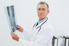 Серьезный доктор с изображением рентгеновского снимка позвоночника в офисе Стоковые Изображения RF