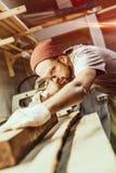 Серьезный плотник работая с планкой тимберса стоковые фото