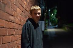 Серьезный подросток полагаясь против кирпичной стены стоковые фотографии rf