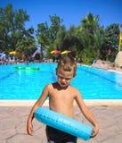 Серьезный ребенк стоит около бассейна стоковая фотография