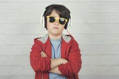 Серьезный ребенок с солнечными очками и наушниками стоковые изображения