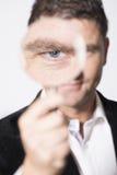 Серьезный смотря человек наблюдая с увеличивать - стекло стоковые изображения rf