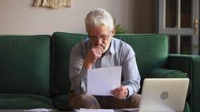 Серьезный старик держа бумажные расчетливые отечественные векселя дома сток-видео