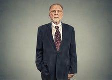 Серьезный старший бизнесмен на серой предпосылке стены стоковые фотографии rf