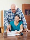 Серьезный старший человек с зрелой женой заполняет внутри вопросник Стоковая Фотография RF