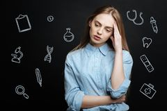 Серьезный студент-медик касаясь ее голове пока думающ о болезни стоковое изображение