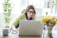 Серьезный студент изучая на компьютере Стоковые Изображения