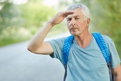 Серьезный сфокусированный сморщенный мужчина с серыми волосами, держит руку около лба, смотрит в расстояние, носит рюкзак, ждет а стоковая фотография