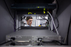 Серьезный техник используя цифровой анализатор кабеля на сервере Стоковые Фотографии RF