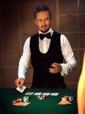 Серьезный торговец кладет последнюю карточку на таблицу стоковое фото