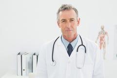 Серьезный уверенно мужской доктор на медицинском офисе Стоковая Фотография RF