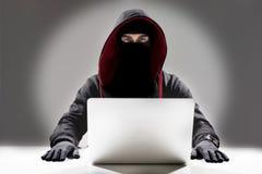Серьезный хакер крадя информацию от компьтер-книжки стоковые изображения