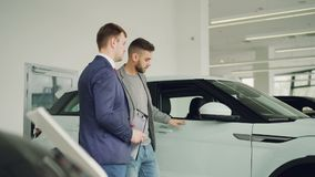 Серьезный человек говорит к автодилеру в выставочном зале мотора обсуждая новую модель автомобиля, salesmanis держа документы сток-видео