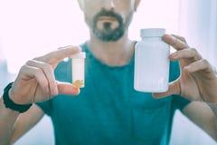 Серьезный человек показывая 2 разного вида таблеток стоковое фото rf
