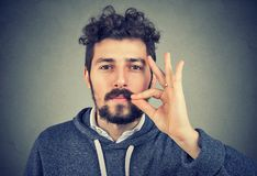 Серьезный человек промелькивая рот держа конфиденциальную информацию Стоковые Фото