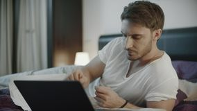 Серьезный человек работая с документами и ноутбуком на софе вечером сток-видео