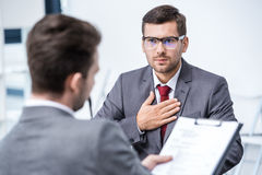 Серьезный человек в костюме и eyeglasses показывать и смотря бизнесмена с доской сзажимом для бумаги Стоковая Фотография RF